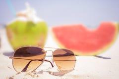 Óculos de sol e fruto na praia tropical arenosa imagens de stock royalty free