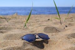 Óculos de sol e fundo do mar Imagens de Stock Royalty Free
