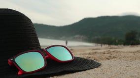 Óculos de sol e largo-borda preta que encontram-se em uma areia No óculos de sol mar, ondas e céu refletidos filme