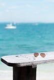 Óculos de sol e oceano azul como o fundo Imagem de Stock