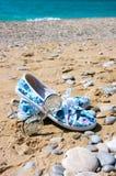 Óculos de sol e sapatas das mulheres na praia Foto de Stock Royalty Free