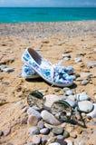 Óculos de sol e sapatas das mulheres na praia Fotografia de Stock Royalty Free