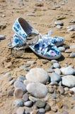 Óculos de sol e sapatas das mulheres na praia Imagens de Stock