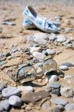 Óculos de sol e sapatas das mulheres na praia Fotos de Stock Royalty Free