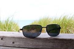 Óculos de sol em trilhos de madeira na praia fotografia de stock