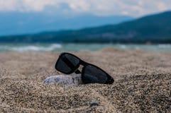 Óculos de sol em uma praia imagem de stock