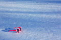 Óculos de sol Heart-Shaped cor-de-rosa na neve imagem de stock royalty free