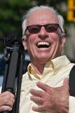 Óculos de sol masculinos de And Laughter Wearing do fotógrafo com tripé imagens de stock royalty free