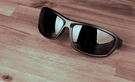 Óculos de sol na madeira Fotografia de Stock Royalty Free