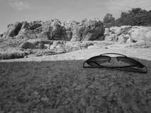 Óculos de sol na praia de pedra Imagem de Stock