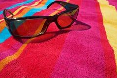 Óculos de sol na toalha de praia fotografia de stock