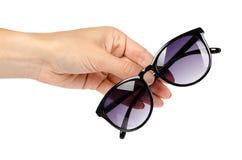 Óculos de sol plásticos à moda com a mão isolada no fundo branco fotografia de stock royalty free