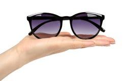 Óculos de sol plásticos à moda com a mão isolada no fundo branco foto de stock
