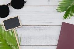Óculos de sol, placa da placa e passaporte pequenos com folhas da samambaia Fotos de Stock Royalty Free