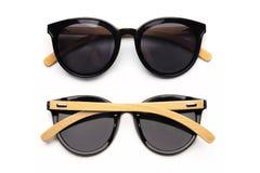 Óculos de sol pretos à moda com a borda de madeira isolada no fundo branco Foto de Stock