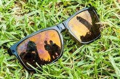 Óculos de sol pretos com lentes polarizadas e os povos refletidos Imagens de Stock