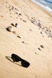 Óculos de sol pretos na areia Imagem de Stock