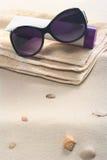 Óculos de sol, protecção solar e toalha na areia Fotografia de Stock