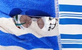 Óculos de sol que encontram-se em uma toalha Imagens de Stock Royalty Free