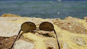 Óculos de sol que encontram-se na cerca de pedra filme