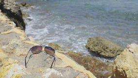 Óculos de sol que encontram-se na cerca de pedra vídeos de arquivo