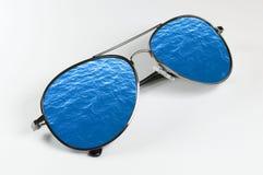 Óculos de sol que refletem a superfície do ` s da água Fotografia de Stock Royalty Free