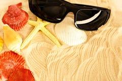 Óculos de sol, seastar e conchas do mar na areia imagens de stock