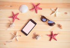 Óculos de sol, smartphone, estrelas do mar e conchas do mar no fundo de madeira Imagem de Stock Royalty Free