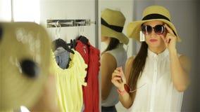 Óculos de sol de tentativa da menina bonita perto do espelho na sala de encaixe Jovem mulher que veste o chapéu engraçado Conceit vídeos de arquivo