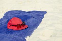 Óculos de sol, um tampão e uma toalha na praia Fotografia de Stock Royalty Free