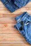 Óculos de sol usados das calças de brim e do aviador sobre de madeira Fotografia de Stock Royalty Free