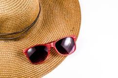 Óculos de sol vermelhos e chapéu da praia isolado no branco Imagem de Stock