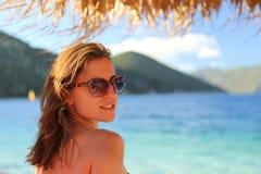 Óculos de sol vestindo da jovem mulher bonita e sorriso na praia Fotografia de Stock Royalty Free