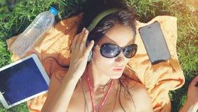 Óculos de sol vestindo da jovem mulher bonita que encontram-se na grama, escutando a música e a música do canto fotos de stock royalty free