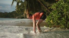 Óculos de sol vestindo da jovem mulher que relaxam em uma praia tropical