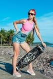 Óculos de sol vestindo da menina loura bonita da forma com suporte do skate contra o mar e a palma fotografia de stock royalty free