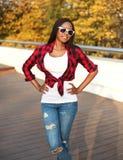 Óculos de sol vestindo da mulher africana nova bonita e camisa quadriculado vermelha na cidade Foto de Stock Royalty Free