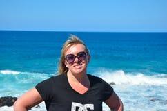 Óculos de sol vestindo da mulher com ondas fotografia de stock royalty free