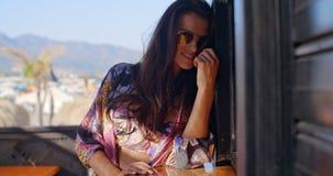 Óculos de sol vestindo da mulher no balcão tropical vídeos de arquivo