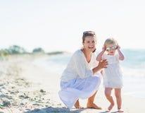 Óculos de sol vestindo de sorriso da mãe e do bebê na praia foto de stock royalty free
