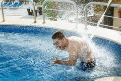 Óculos de sol vestindo do homem considerável novo que apreciam o jato da água Imagem de Stock