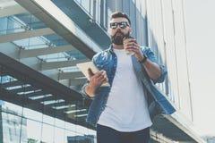 Óculos de sol vestindo do homem de negócios farpado novo que andam abaixo da rua da cidade, guardando a xícara de café e o tablet imagem de stock