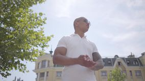 Óculos de sol vestindo do homem do Oriente Médio calvo bem sucedido seguro do retrato e t-shirt branco Olhares consideráveis do i filme