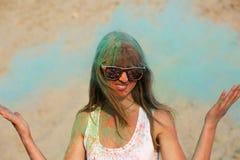 Óculos de sol vestindo do modelo novo maravilhoso que levantam com explosão em torno de seu pó azul de Holi no deserto fotos de stock