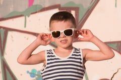 Óculos de sol vestindo do rapaz pequeno engraçado e camisa listrada no fundo dos grafittis foto de stock