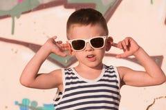 Óculos de sol vestindo do rapaz pequeno fresco e veste listrada no fundo dos grafittis imagem de stock royalty free