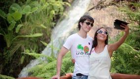 Óculos de sol vestindo dos pares felizes que tomam a foto do selfie no fundo bonito da cachoeira Lagoa esmeralda e plantas exótic video estoque