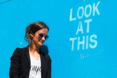 Óculos de sol vestindo modelo do moderno que levantam ao lado de Lo Imagem de Stock