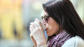 Óculos de sol vestindo de sorriso elegantes da mulher bonita do close-up que relaxam o café bebendo exterior filme