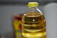 Óleo amarelo em uma garrafa transparente plástica imagens de stock royalty free
